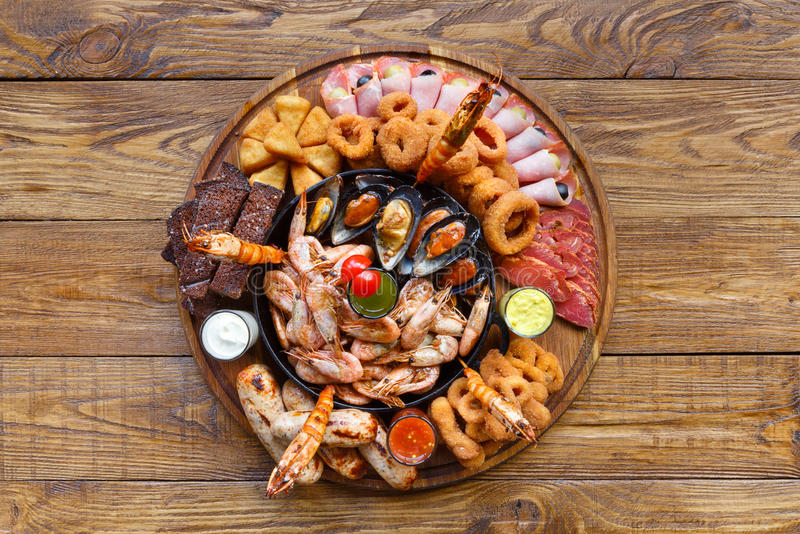 Seafood platter on wooden table background. Seafood and meat platter. Mediterranean cuisine restaurant food, fried calamari rings, king prawns, mussels, oysters stock image