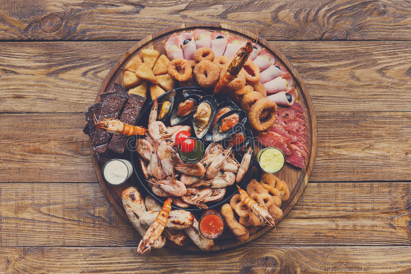 Seafood platter on wooden table background. Seafood and meat platter. Mediterranean cuisine restaurant food, fried calamari rings, king prawns, mussels, oysters stock photos