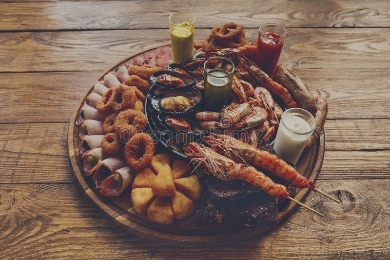 Seafood platter on wooden table background. Seafood and meat platter. Mediterranean cuisine restaurant food, fried calamari rings, king prawns, mussels, oysters stock photo