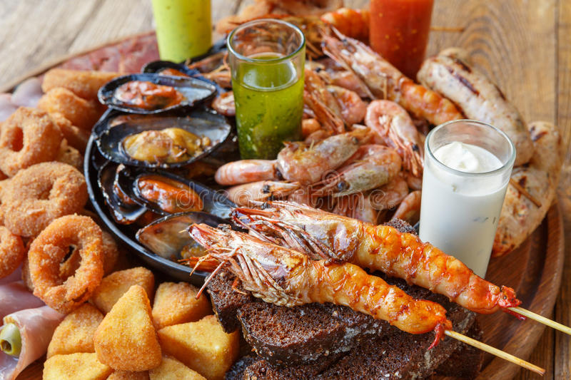 Seafood platter on wooden table background. Seafood platter. Mediterranean cuisine restaurant food closeup, fried calamari rings, king prawns, mussels, oysters royalty free stock photo