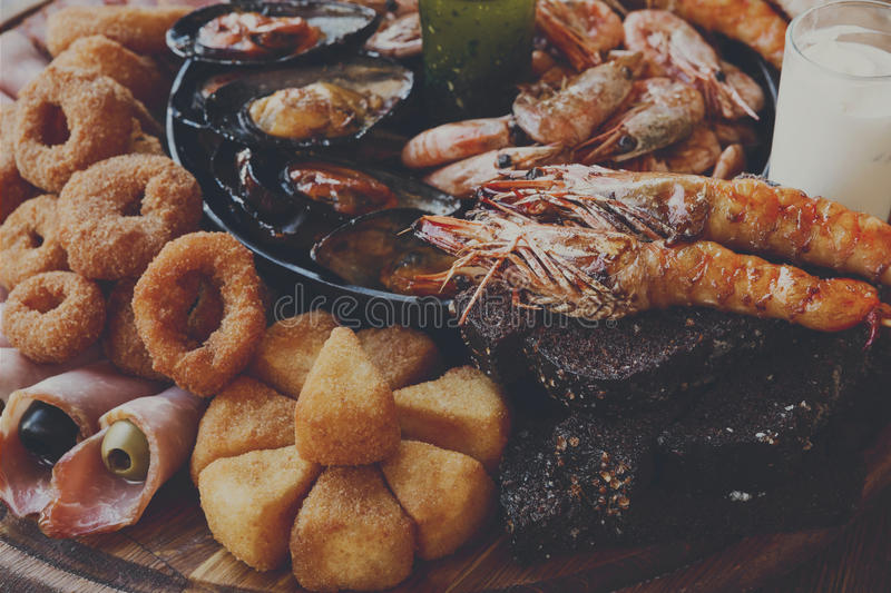 Seafood platter on wooden table background. Seafood platter. Mediterranean cuisine restaurant food closeup, fried calamari rings, king prawns, mussels, oysters stock image