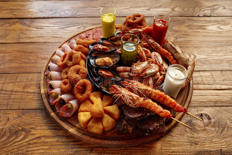 Seafood platter on wooden table background. Seafood platter. Mediterranean cuisine restaurant food, fried calamari rings, king prawns, mussels, oysters royalty free stock image
