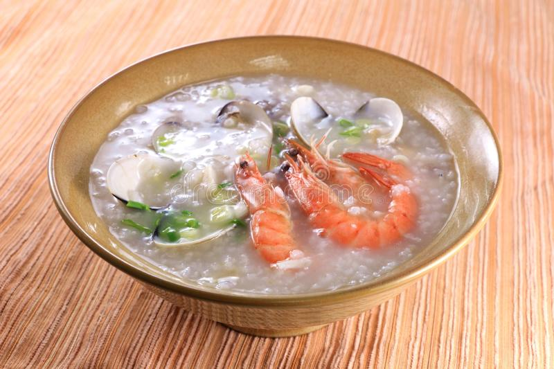 Seafood porridge with shrimp, clams, mussel in chinese bowl royalty free stock photo