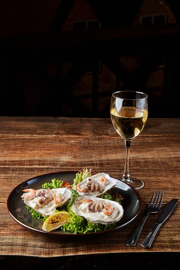 Seafood. Restaurant cuisine, healthy delicatessen food. Oysters, shrimps, octopus in white cream sauce in the shell of. Oysters. Original serving of ready meals royalty free stock image
