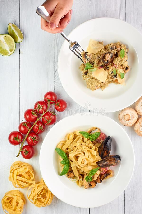 Seafood risotto and fettuccine pasta at white wooden table top. woman hand with fork is takes some of rice stock photo