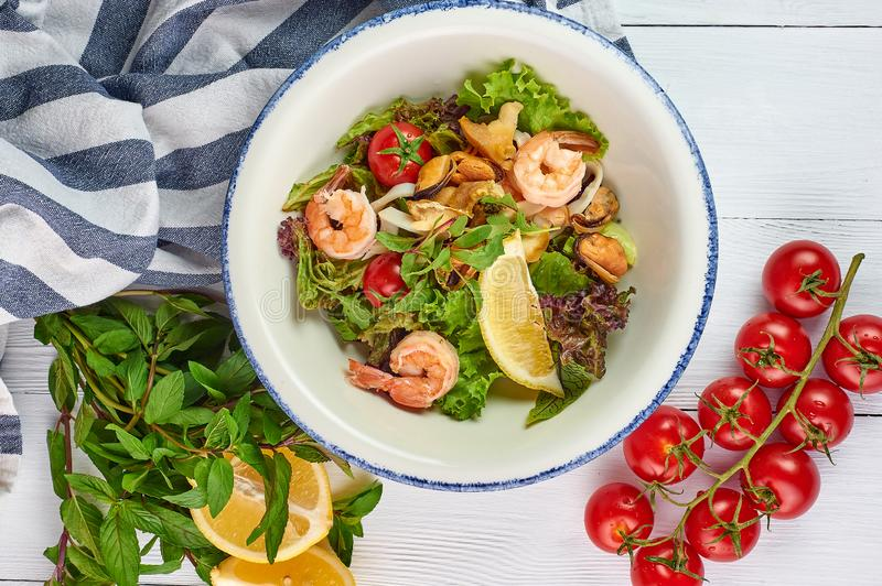 Seafood salad decorated with cherry tomatoes mint and lemon at white wooden table top stock photo
