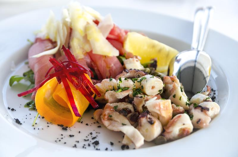 Seafood salad served in white plate closeup. Octopus and tuna fish with lemon salad appetizer on restaurant table stock image