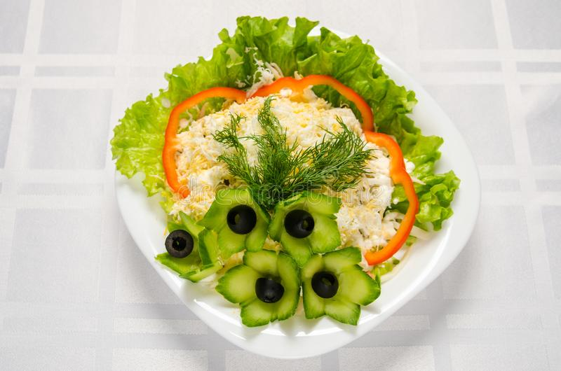 Seafood salad - squid, crab sticks, cucumbers, eggs, mayonnaise, cheese, lettuce, tomato, olives and greens on white dish royalty free stock photos