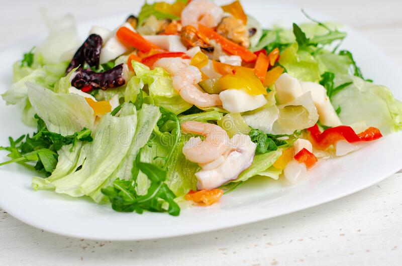 Seafood salad with vegetables and lettuce on white plate. Mediterranean delicacy food. Seafood salad with vegetables and lettuce on white plate. Mediterranean royalty free stock photos