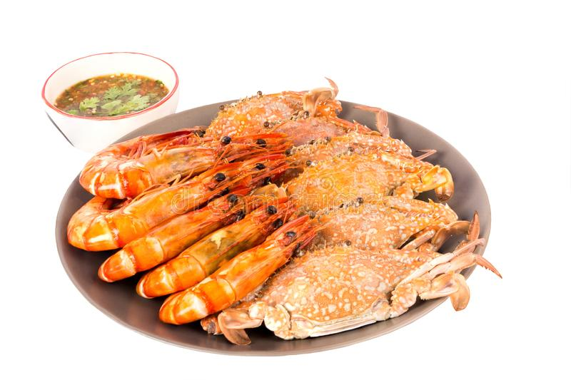 Seafood, shrimp and crab in the dish. And sauce in the cup royalty free stock image