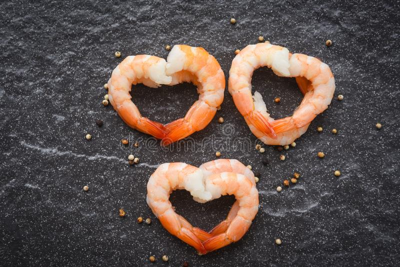 Seafood shrimps heart shape - Cooked shrimp prawns on dark background - valentines dinner romantic love food and love cooking stock photography