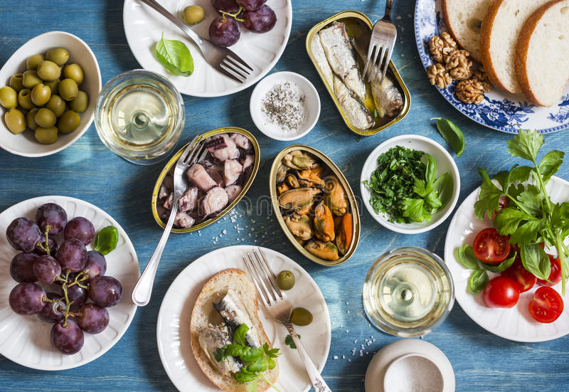 Seafood snacks table - canned sardines, mussels, octopus, grape, olives, tomato and two glasses white wine on wooden table, top vi royalty free stock photography
