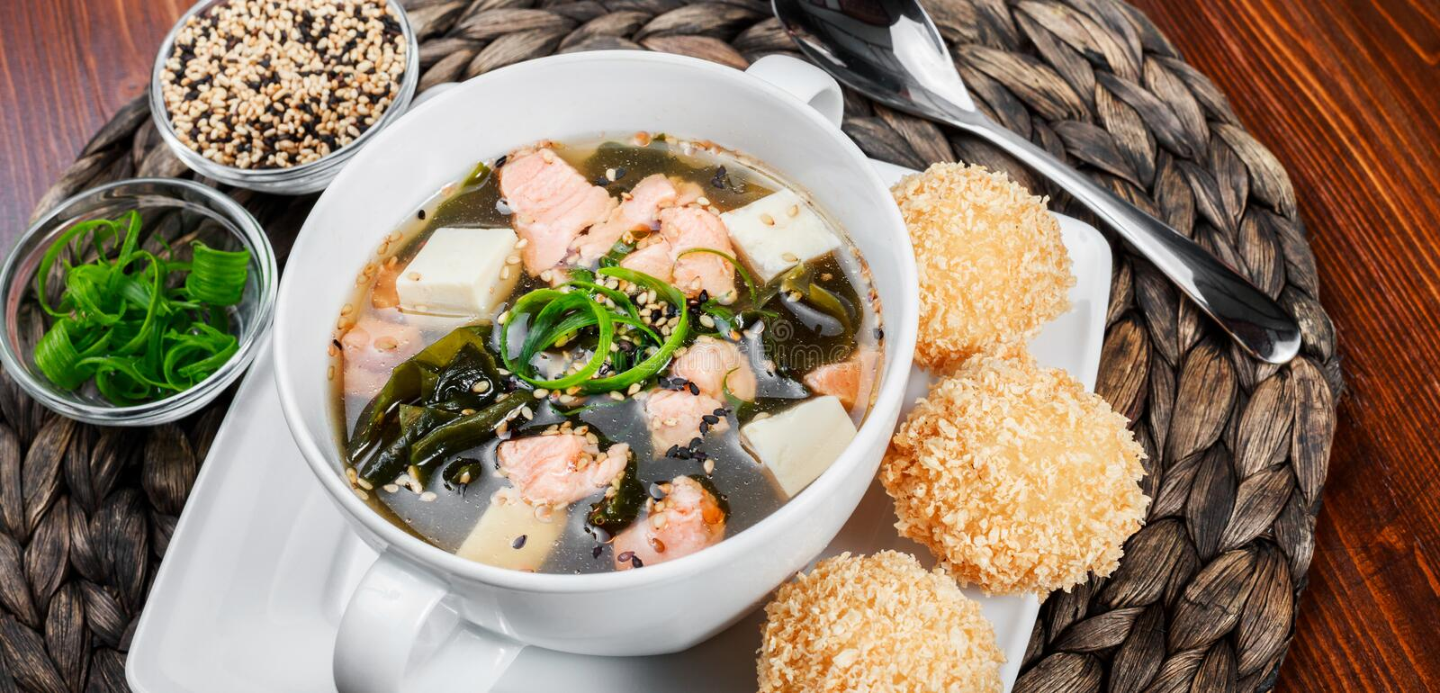 Seafood Soup with salmon, cheese, seaweed, sesame and bread on plate on wooden background. Mediterranean food. Ingredients on table stock images