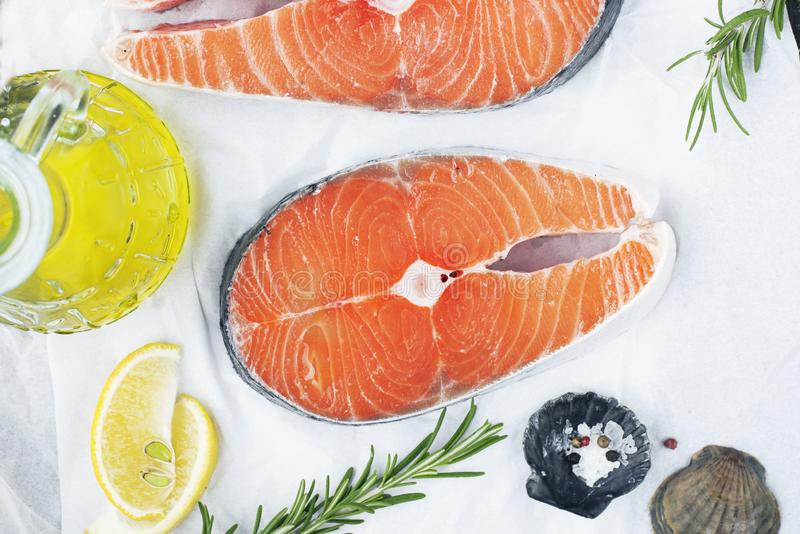 Seafood. Steaks of wild sea salmon on a light background with sea salt, rosemary and lemon. Top view. royalty free stock photo