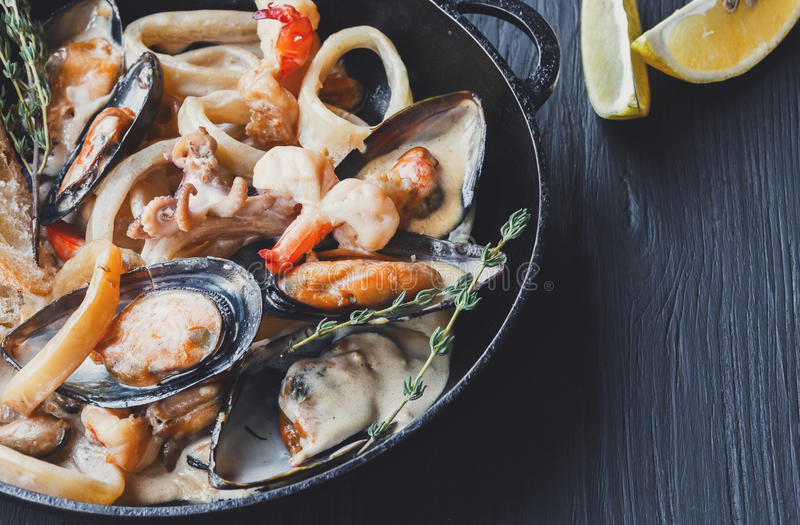 Seafood Stew in Saucepan closeup on dark wood background. Seafood Stew in Saucepan closeup. Authentic italian restaurant cuisine, healthy delicatessen food royalty free stock photography