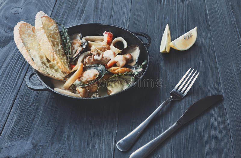 Seafood Stew in Saucepan on dark wood background stock image
