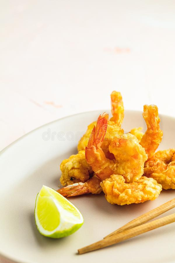 Seafood tempura dish of traditional asian cuisine. Fried Shrimps tempura in light plate on pink or peach concrete surface background. Copy space for you text stock image