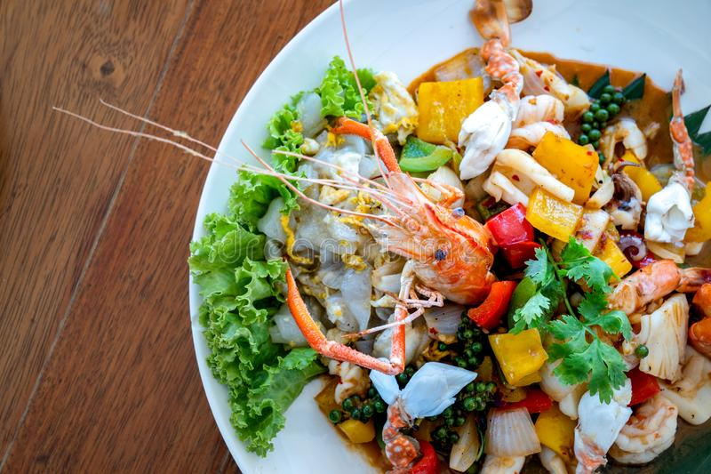 Seafood Thai mixxed together between boiled shrimp, crab, squid and colourful vegetable in dish on wood table in restaurant royalty free stock photo