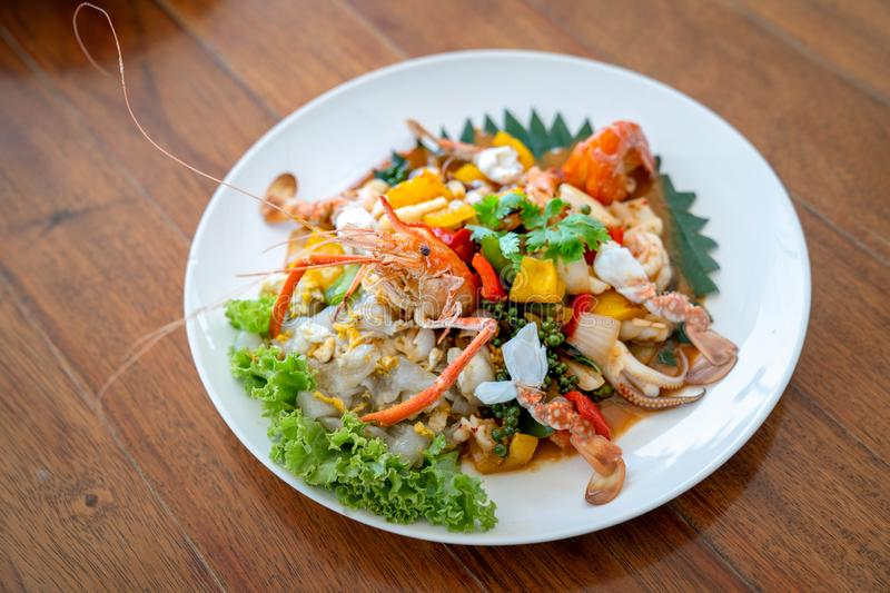 Seafood Thai mixxed together between boiled shrimp, crab, squid and colourful vegetable in dish on wood table in restaurant stock photo