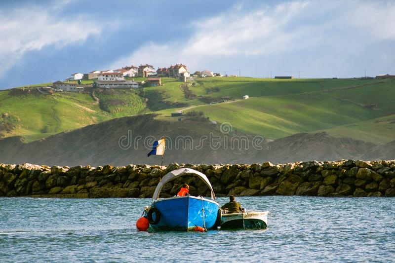 Sailors working on a boat in the water and a mountain in the  background on a cloudy day with blue sky. Fishermen working on boats with a stone wall in the stock photos