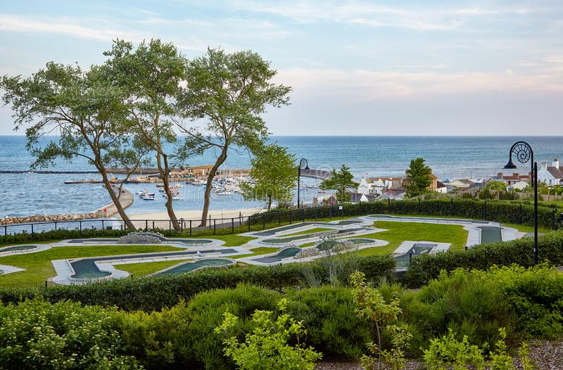 The Seafront gardens of Lyme Regis. West Dorset. England. The mini-golf field in the Seafront gardens (Langmoor and Lister Gardens) with the beautiful view of royalty free stock photos