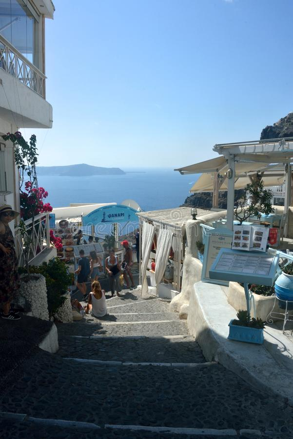 street view of Fira with tourists walking and looking the shops stock image
