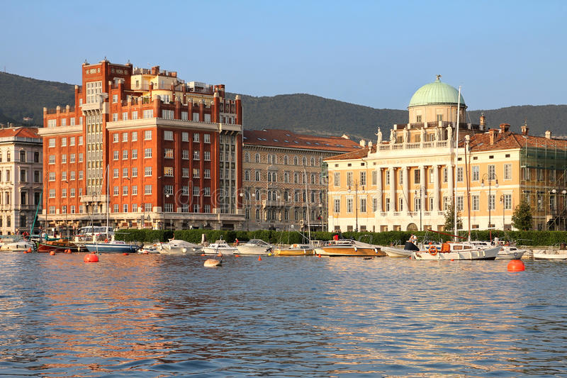 Seafront in Trieste, Italy. Golden hour over the seafront of Trieste, Italy with 2 impossing and beautiful palaces: Palazzo Aedes (in red) and Palazzo Carciotti stock photo