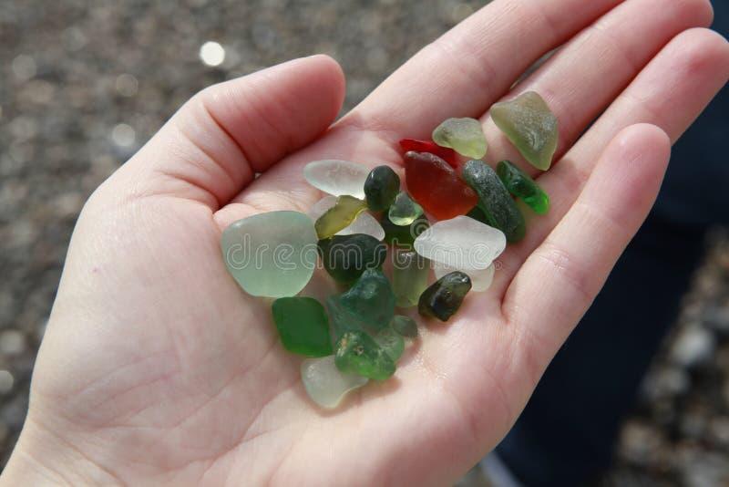 Seaglass verdes, marrons, brancos na mão foto de stock