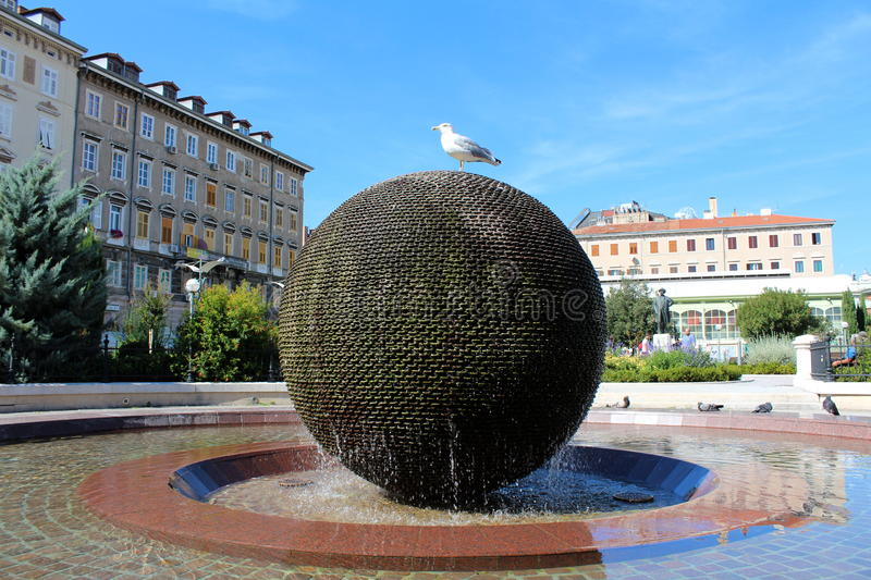 Seagull sitting on a spherical water fountain. White and grey seagull sitting calmly on a spherical water fountain on a city square in front of old buildings in stock photos
