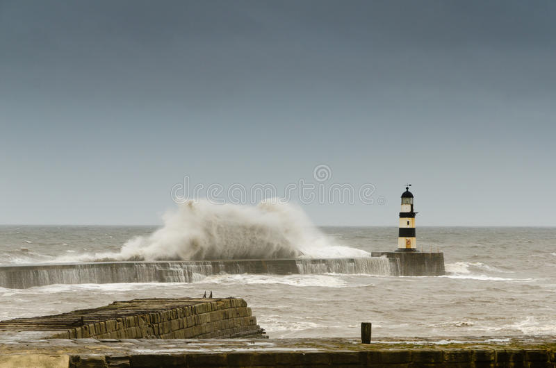 Seaham lighthouse with crashing waves. Crashing waves over the north pier in a rough sea at Seahan Harbour royalty free stock photography