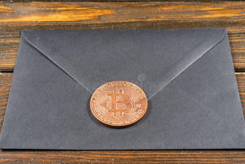 Seald negro por el sobre del bitcoin en fondo azul claro imagenes de archivo