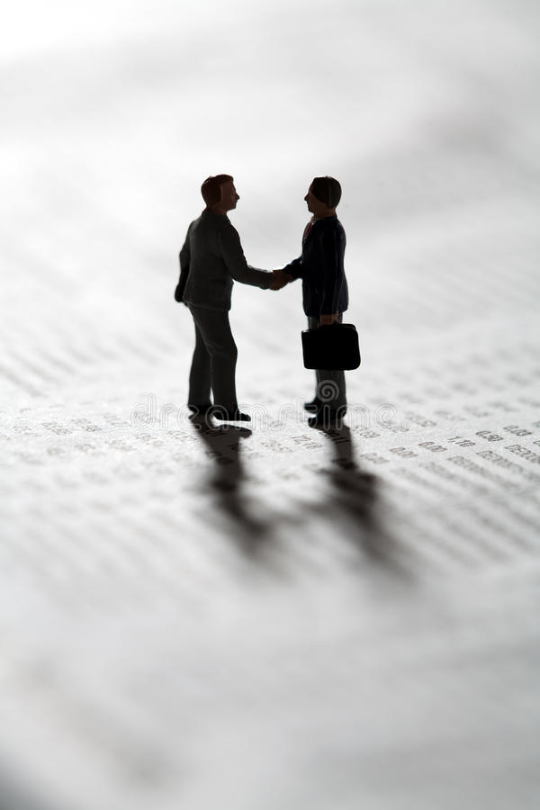 Sealing a business transaction with a handshake. Two tiny miniature figurines of businessman standing in silhouette on a statistical document sealing a business stock photo