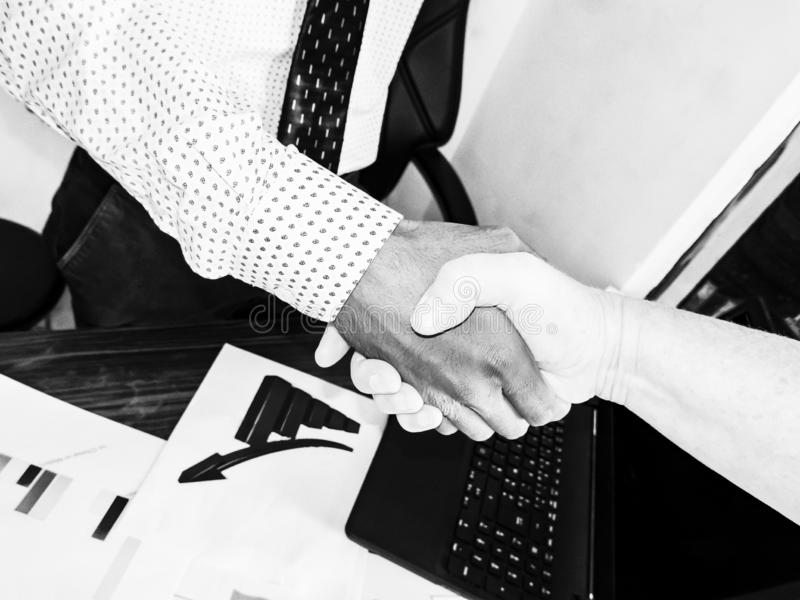 Sealing a deal. Top view of an indian man and caucasian woman shaking hands in office. Multi racial relationship stock photography