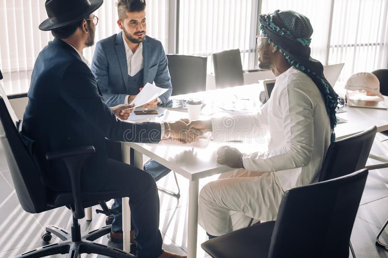Sealing a deal. Top view of three men sitting at the desk and shaking hands royalty free stock photos