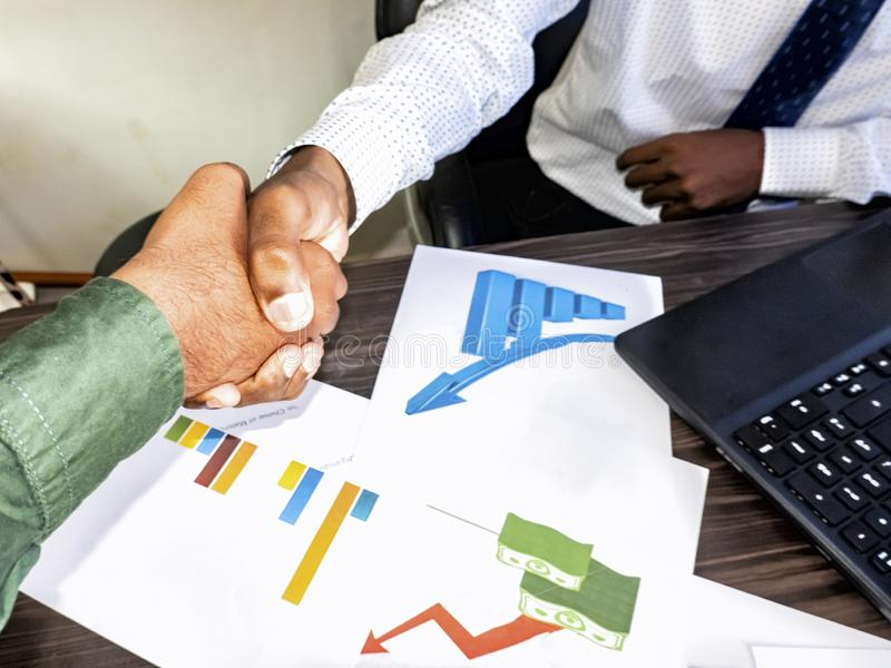 Sealing a deal. Top view of two indian men sitting at the desk and shaking hands stock photography