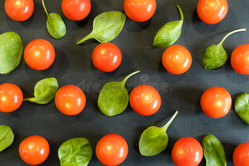 Seamless pattern with cherry tomatoes and spinach. Abstract background. Tomato the black background. Group of red ripe. Seamless pattern with cherry tomatoes and royalty free stock photo