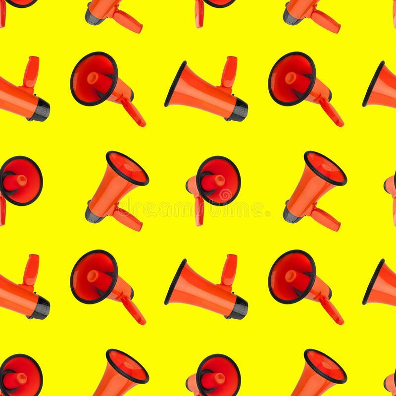 Seamless pattern of orange megaphones on yellow background isolated closeup, loudspeakers backdrop design, loudhailers ornament royalty free stock photography