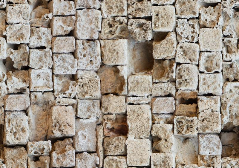 Seamless pattern of partially destroyed masonry wall of limestone blocks. Background texture of weathered ancient brick royalty free stock photo