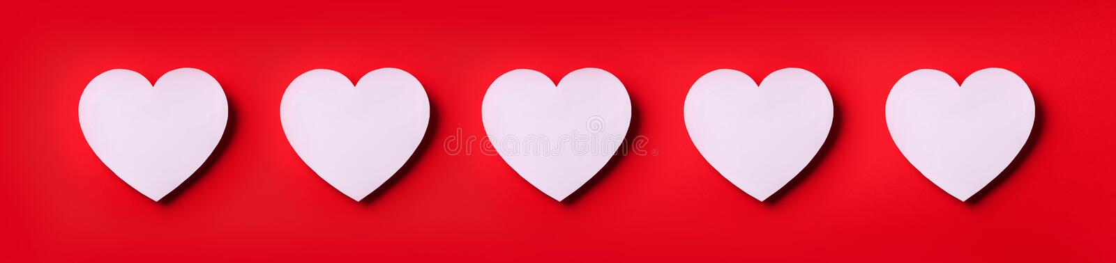 Seamless pattern of white hearts on red background. Top view. Valentine`s Day. Love, date, romantic concept. Banner.  stock images