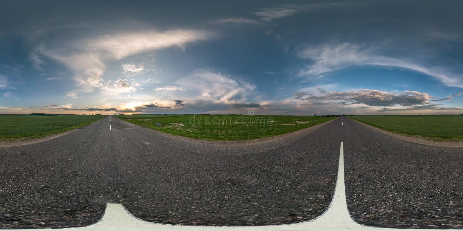 Seamless spherical hdri panorama 360 degrees angle view on asphalt road among fields in summer evening sunset with awesome clouds. In equirectangular projection stock images