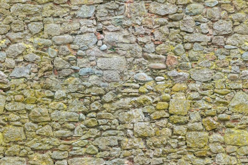 Aged or ancient yellow bricks and stones wall. Seamless brick background. Seamless surface structure of brickwork. Ancient yellow bricks and stones wall royalty free stock images