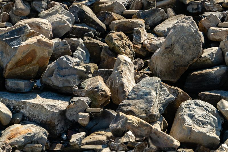 Seamless texture with sea stones and rocks of different sizes as original background. Natural stone of black, gray royalty free stock image