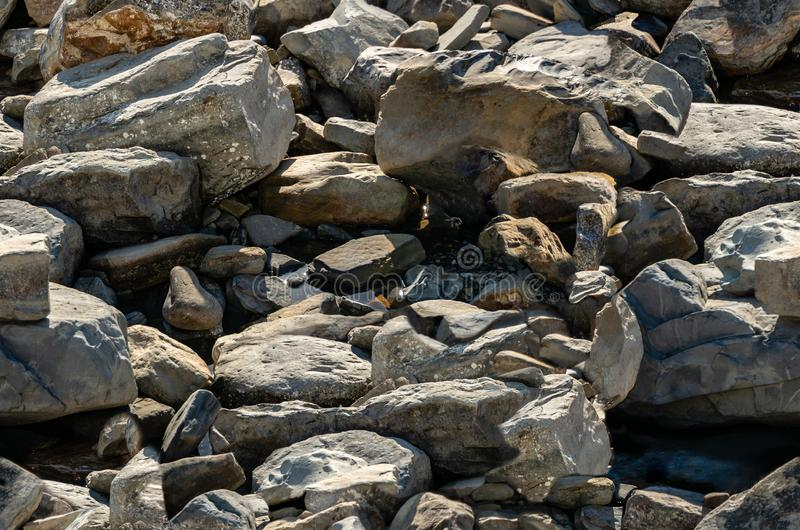Seamless texture with sea stones and rocks of different sizes as original background. Natural stone of black. Gray and brown on the Black Sea coast. Background stock image