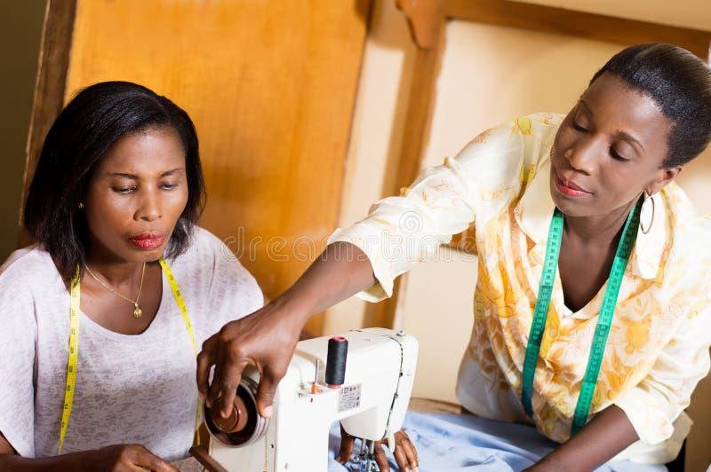 Seamstress και ο εκπαιδευόμενός του στην εργασία στο εργαστήριο στοκ φωτογραφίες με δικαίωμα ελεύθερης χρήσης