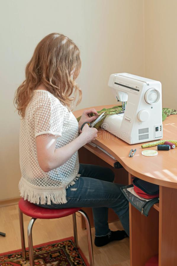 Seamstress with blonde hair in white t shirt sitting on blue chair near wooden table with sewing machine, cutting fabric. Side view of seamstress with blonde royalty free stock photo