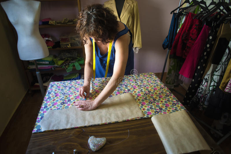 Seamstress cutting patterns. In tailoring stock images
