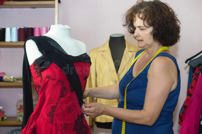 Seamstress doing arrangements. In a dress stock image