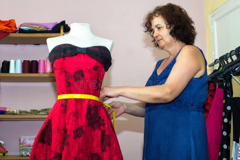 Seamstress doing arrangements in a dress. Woman seamstress doing arrangements in a dress stock photo