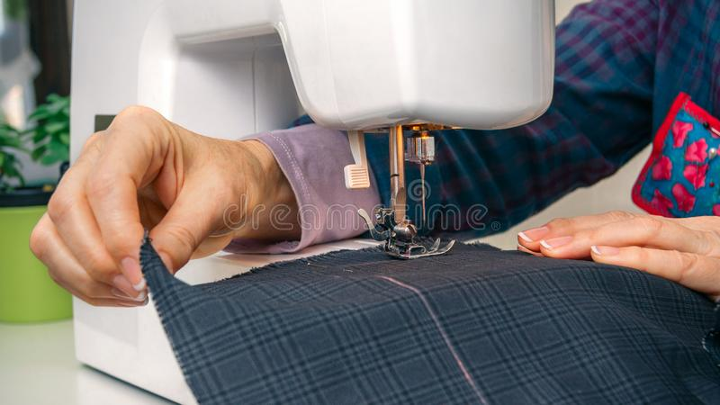 Seamstress hands working on a sewing machine. Closeup of seamstress hands working with clothing item on a sewing machine royalty free stock image