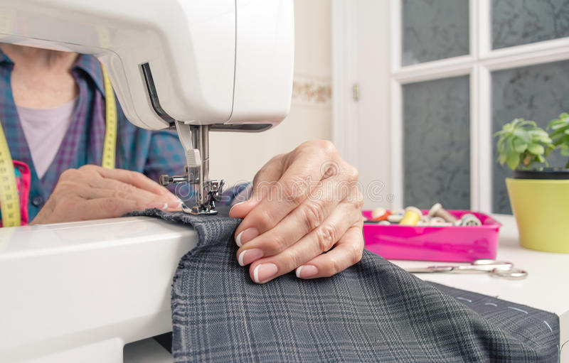 Seamstress hands working on a sewing machine. Closeup of seamstress hands working with clothing item on a sewing machine stock photos